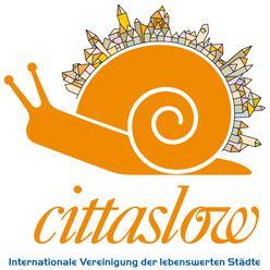 """Das Logo der Cittaslow zeigt eine orangene Schnecke mit einer Stadt-Silhouette auf dem Rücken. Unten steht der Slogan """"Internationale Vereinigung der lebenswerten Städte""""."""