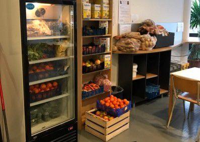 Das Bild zeigt einen Kühlschrank, ein Regal und Kisten mit Gemüse und Obst.