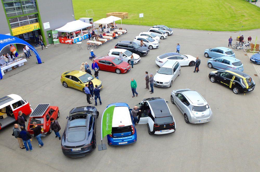 Das Bild zeigt einen Platz mit verschiedenen E-Autos und Ständen.
