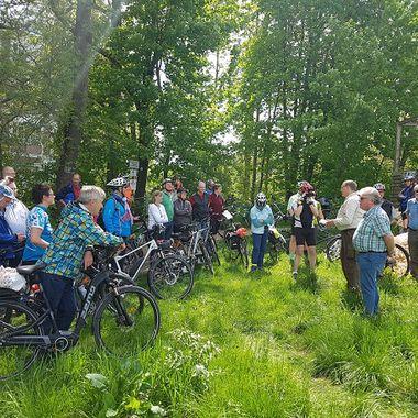 Viele Personen stehen mit oder auf Fahrrädern auf einer grünen Wiese. Im Hintergrund sind ein Holzgerüst und hohe Bäume zu sehen
