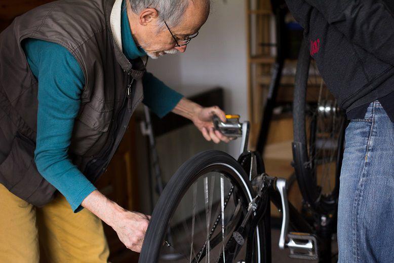Zwei Personen beugen sich über ein umgedrehtes Fahrrad. Sie sind gerade dabei es zu reparieren.