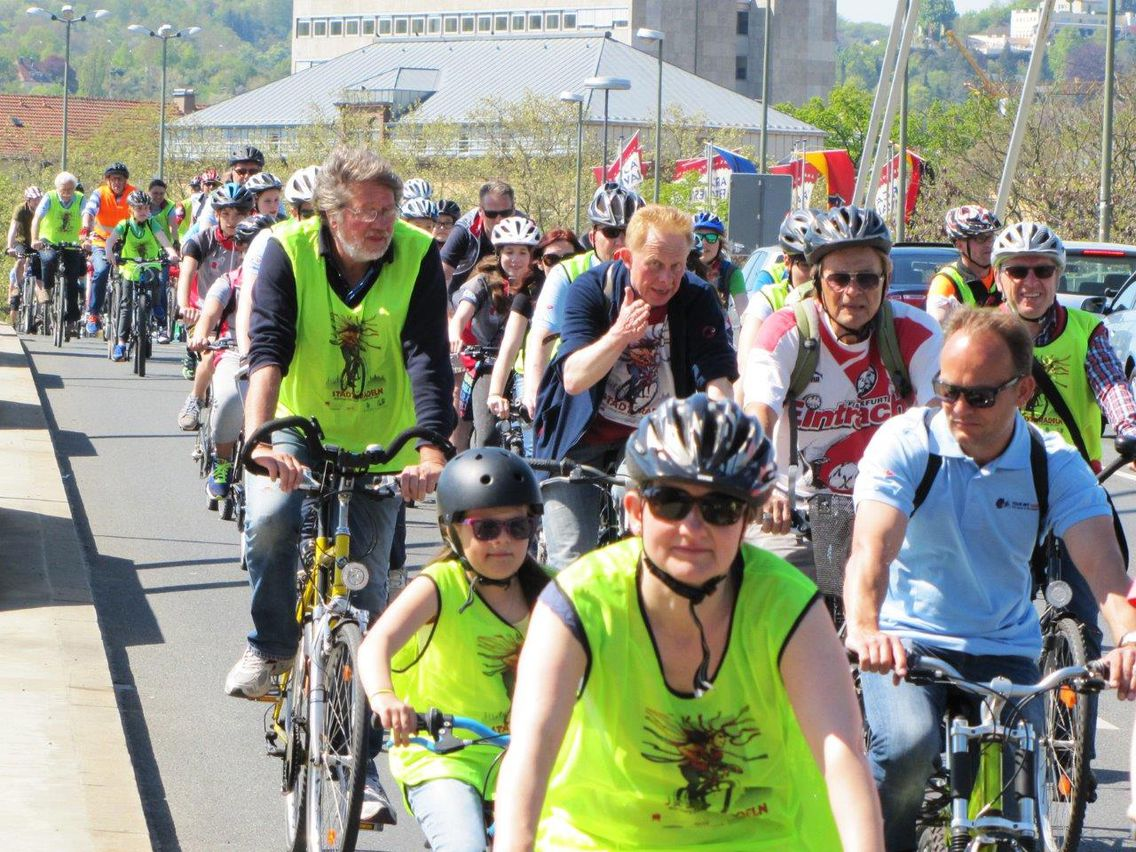 Viele Menschen auf Fahrrädern fahren auf einer Straße. Einige haben gelbe Warnwesten an. Im Hintergrund ist ein großes Haus zu sehen.