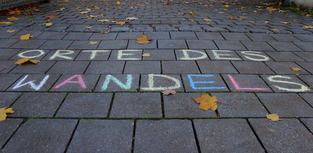 """Ein geplasterter Weg auf dessen Steinen der Schriftzug """"Orte des Wandels"""" mit bunter Kreide geschrieben steht"""