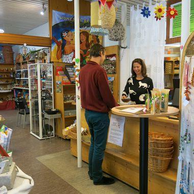 Zwei Personen stehen vor der Kasse im Weltladen. Um Sie ehrum die vielen Produkte, die es im Laden zu kaufen gibt.