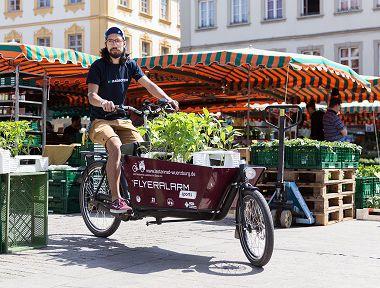 Eine Person fährt mit einem Lastenrad durch ein paar Stände eines Wochenmarktes.