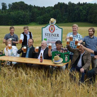 Einige Personen sitzen auf einer Bierbank mitten im Feld bei einer Bio-Bierverkostung (Foto: Claudia Heid, LfL)