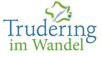 Schriftzug in den Farben Grün und Blau und darüber eine abstrakte Abbildung von München mit der Lokalisation von Trudering.