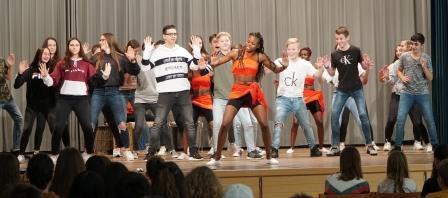 Mehrere Jugendlichen stehen auf einer Bühne und führen einen Tanz auf