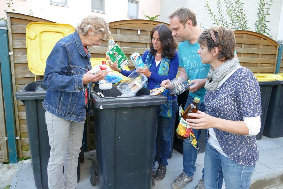 Vier Bürger*innen in Neuburg begutachten den Plastikmüll in einer Gelben Tonne