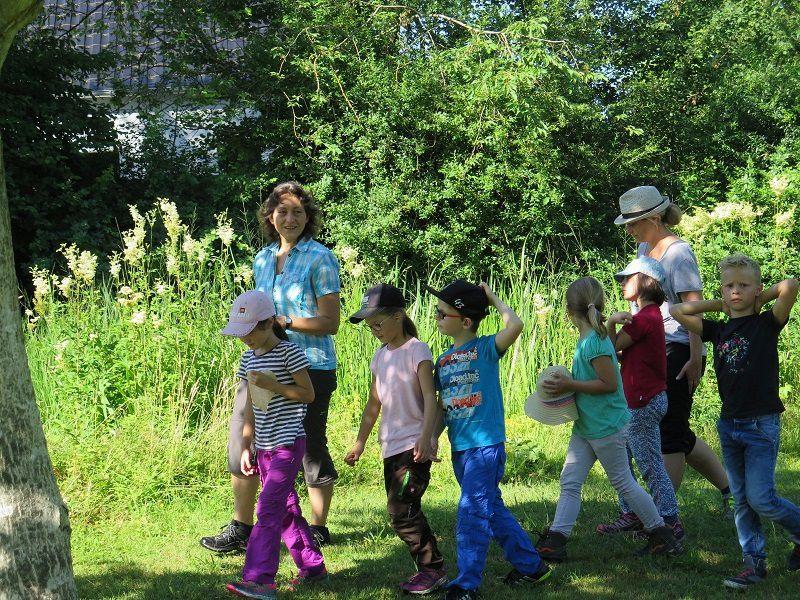 Zwei Erwachsene und sechs Kinder während eines Ausflugs auf einer Wiese im Sonnenschein