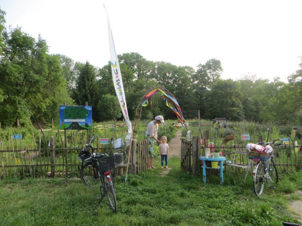 Der Eingang zum Garten ist dargestellt. Es gibt einen Holzzaun und ein großes Tor aus Weidenruten, hinter welchem eine Frau und ein Kind stehen.