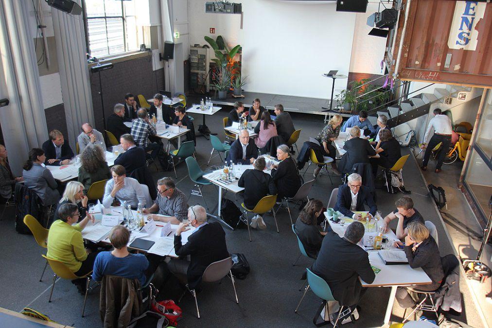 Der Nachhaltigkeitsrat Freiburg bei einer Sitzung. Die Personen sitzen in Kleingruppen an tischen und diskutieren über Themen der Nachhaltigkeit.