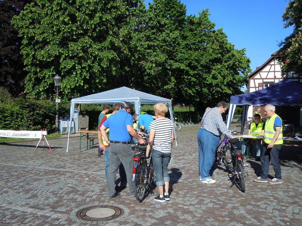 Zwei Gruppen stehen jeweils um ein Fahrrad und reden miteinander. Im Hintergrund stehen zwei Pavillons der Lokalen Agenda 21 Allensbach vor grünen Bäumen und einem Fachwerkhaus.