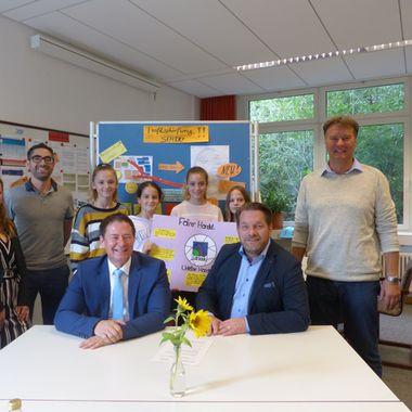 Das Bild zeigt mehrere Menschen bei der Unterzeichnung zur Nachhaltigen Schule.