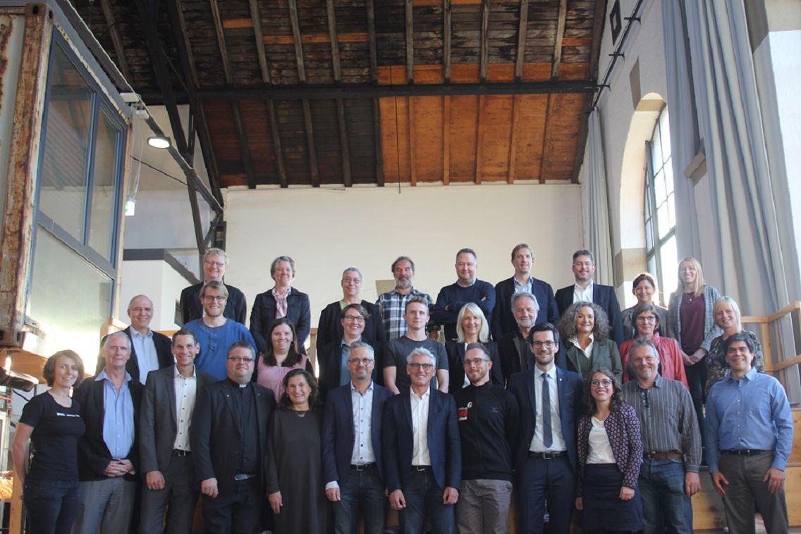 Ein Gruppenfoto des Nachhaltigkeitsrats Freiburg. Die Mitglieder*innen sind an einer Treppe aufgereiht.