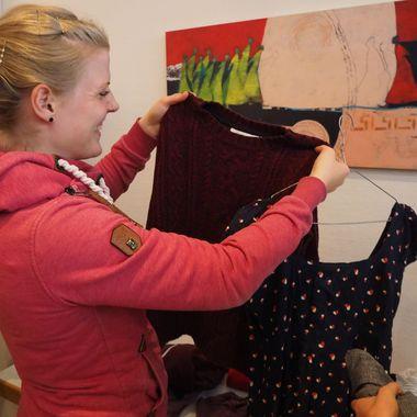 Das Bild zeigt eine Frau die sich Kleidung an einer Kleiderstange ansieht.