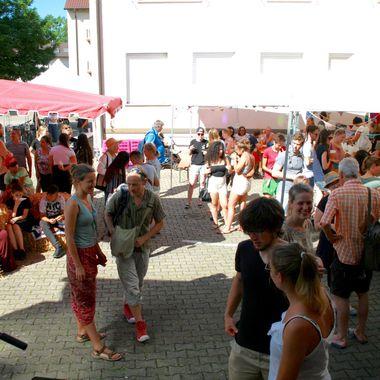 Das Haus des Engagements in Freiburg von außen. Im Hof tummeln sich viele junge und alte Leute bei einem Fest.