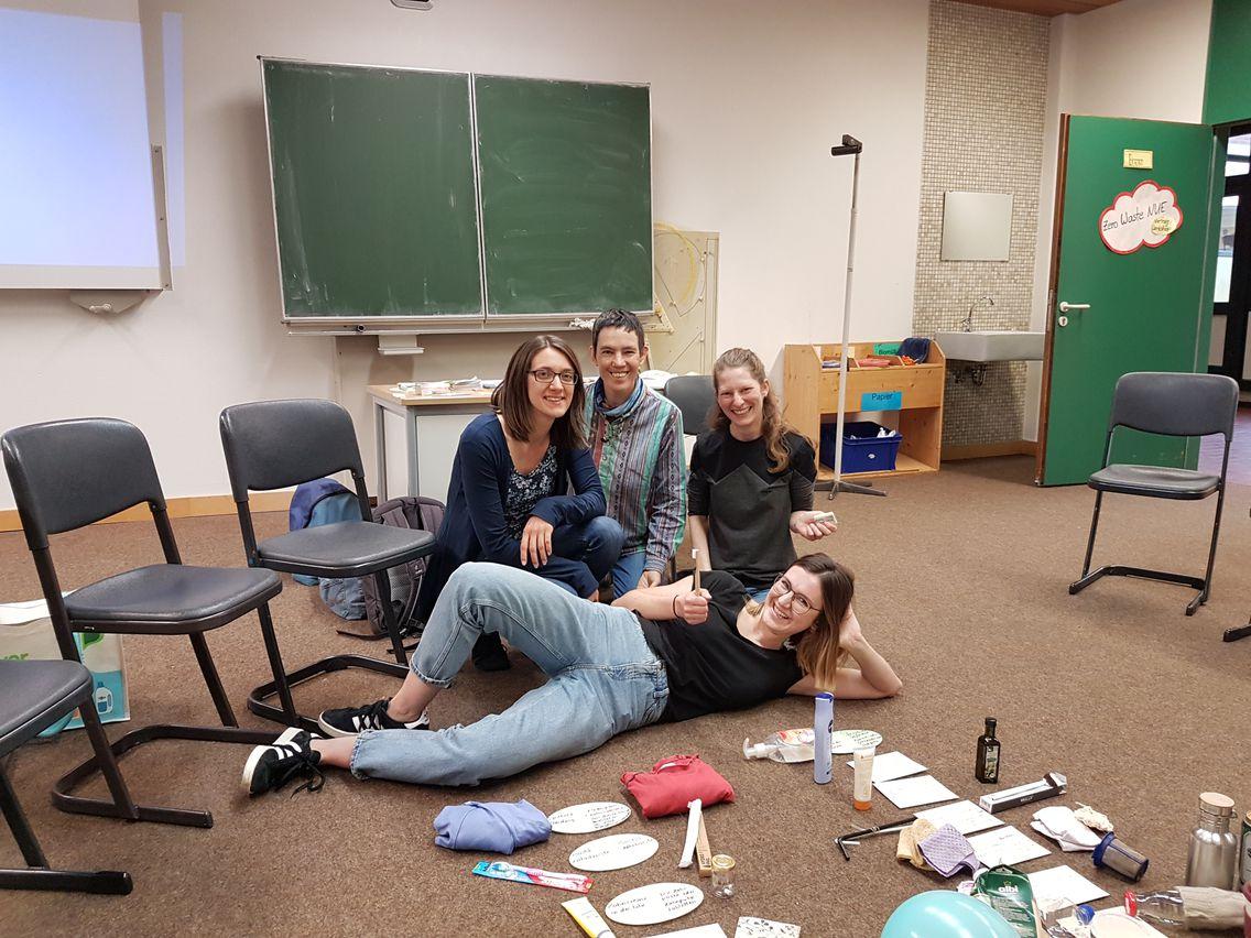 Eine Vierergruppeposiert für das Foto in einem Klassenzimmer. Im Hintergrund die Tafel und stühle. Vor ihnen liegen zero waste Produkte.